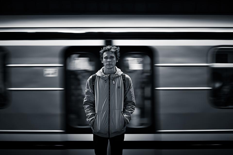 Mladý muž v metre čaká na prichádzajúci vlak